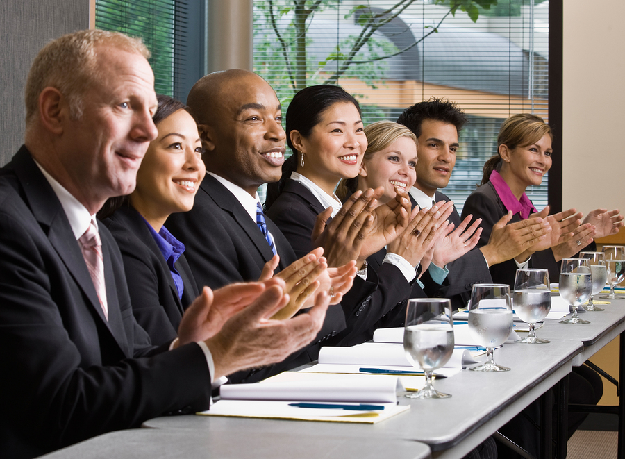 Multi-ethnic co-workers sitting in a row, applauding at conferen