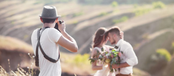 wedding photographer filming bride and groom