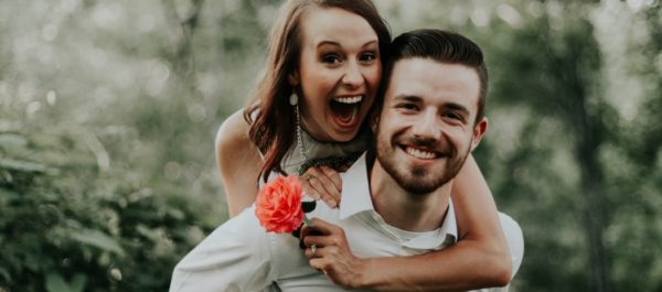 Wedding Planning - Woman Holding a Flower And Piggybacking On Man